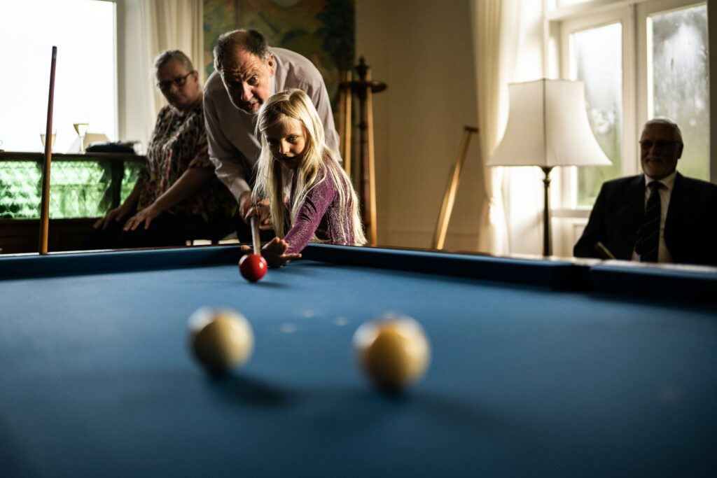 Grandpa teaching his granddaughter how to hold a pool stick