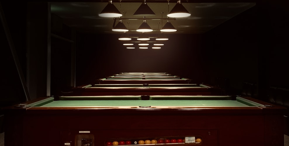 Pool tables lined up in a recreational center