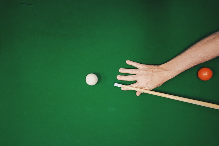 Close up of a person about to shoot a pool ball