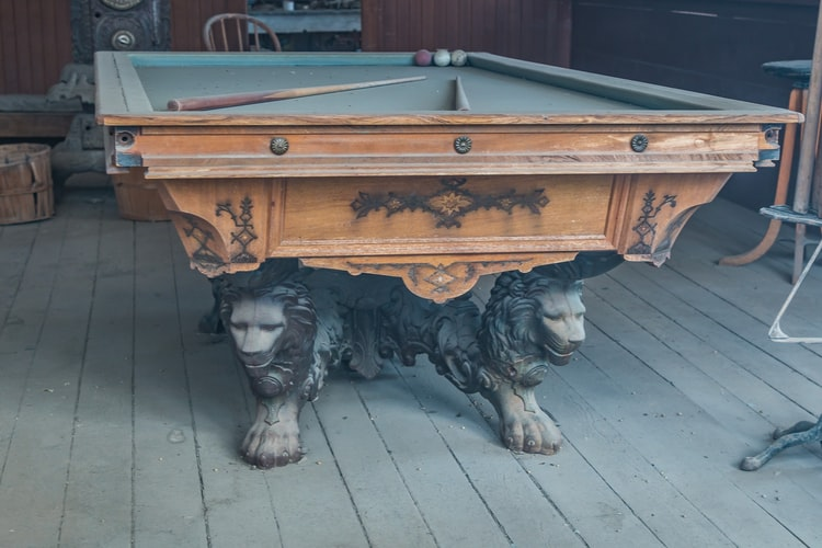 Ceramic lion sculpture adding considerable weight to a pool table