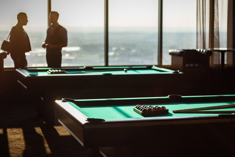 Two people taking near two pool tables