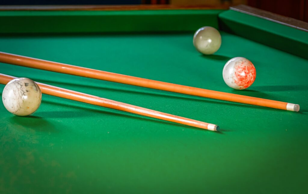 Three cue balls and two cue sticks on a pool table