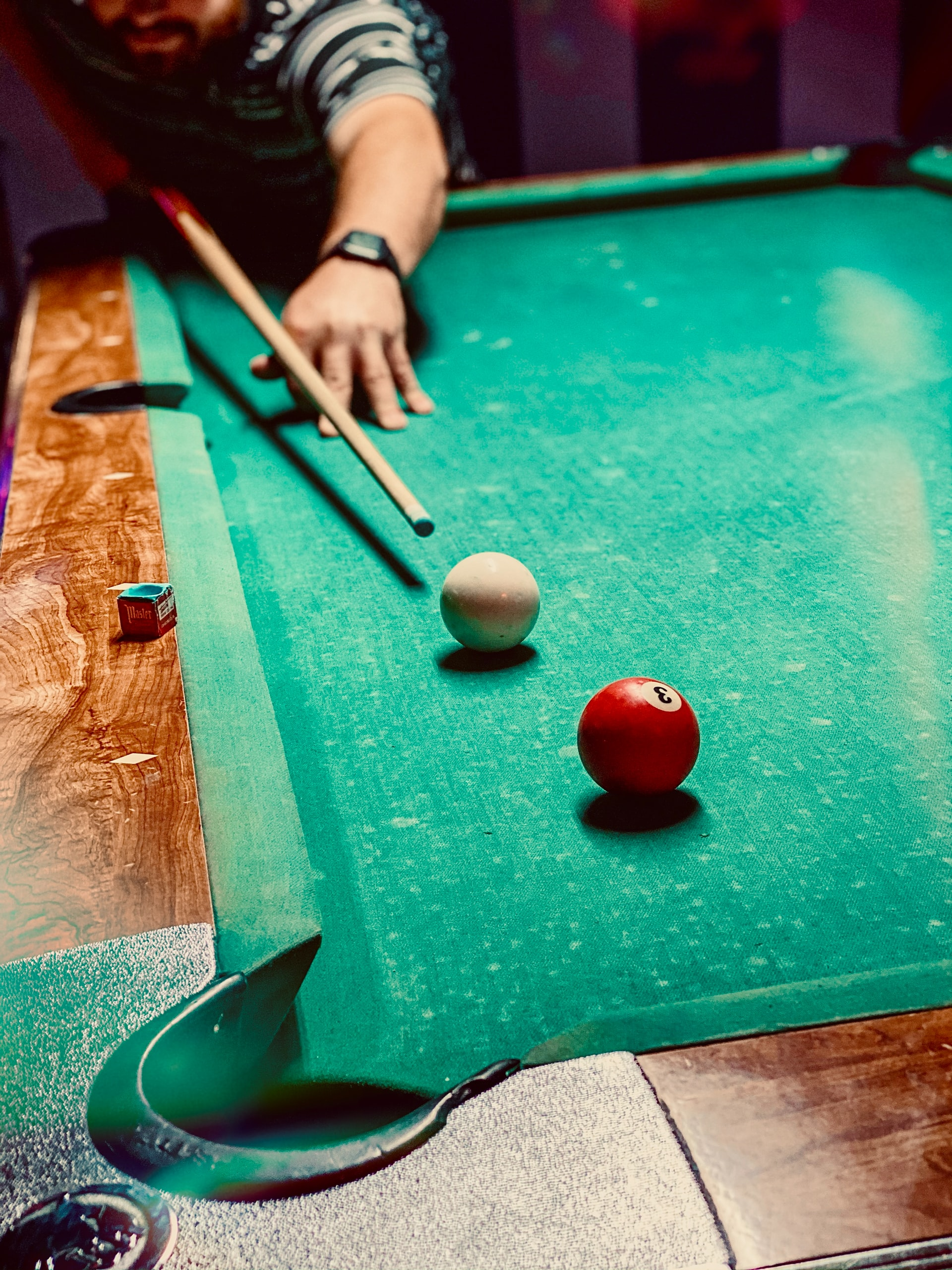 Man getting ready to hit the cue ball with pool cue