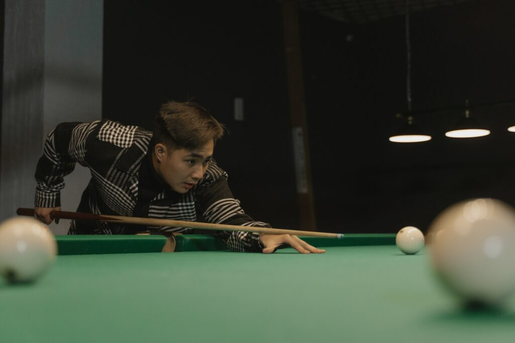 Man wearing a black and white coat playing billiards