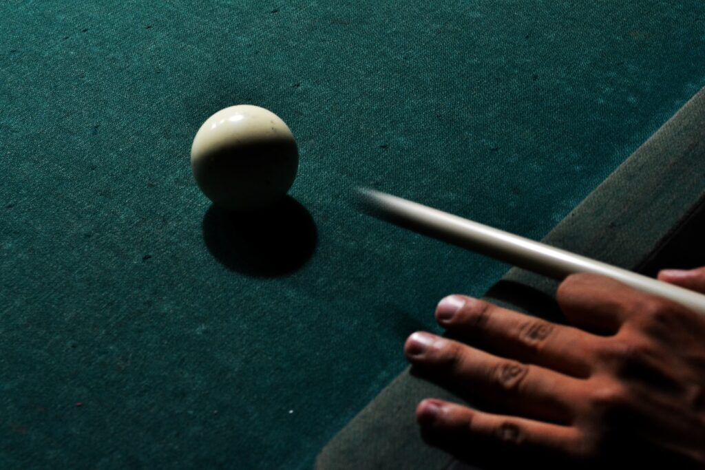 Person hitting cue ball with cue stick