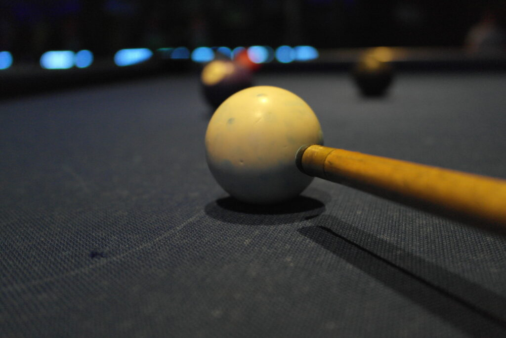 Pool cue aiming at a ball