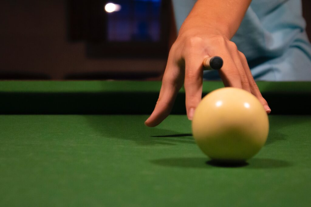 Person pointing a cue stick to the cue ball