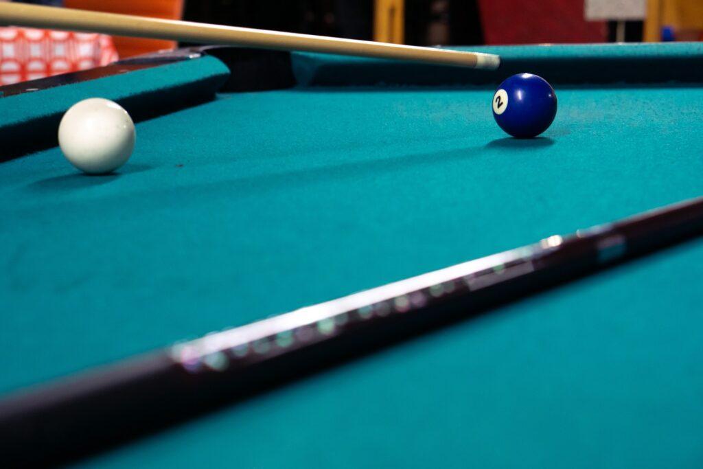 Two billiard balls on a green pool table