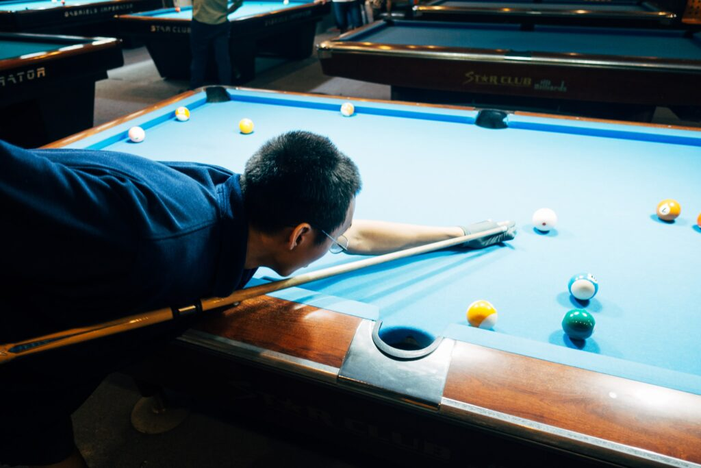 Man wearing a glove while playing pool