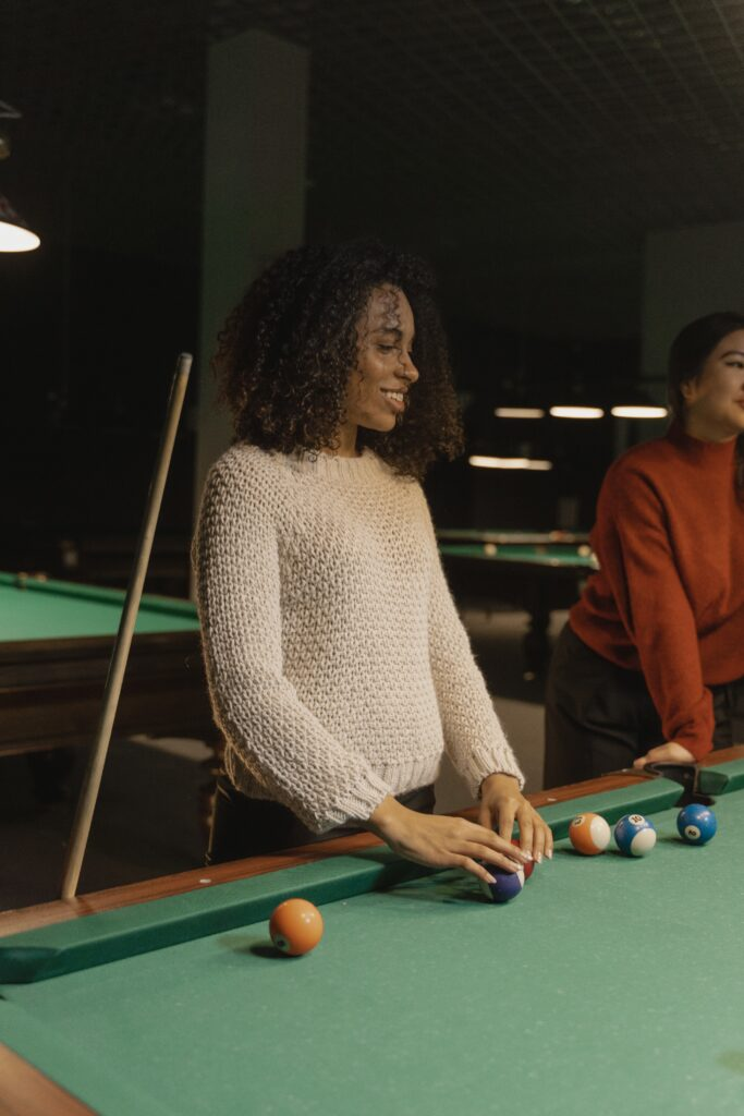 Woman and friends playing a game of pool