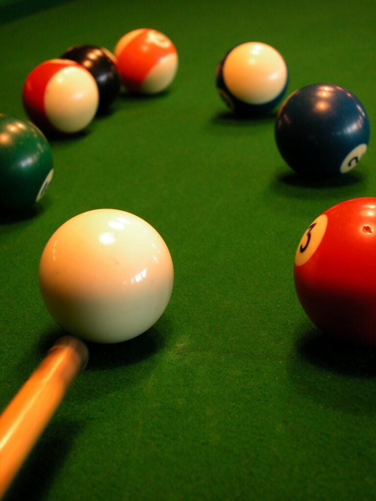 Pool cue aiming at a ball