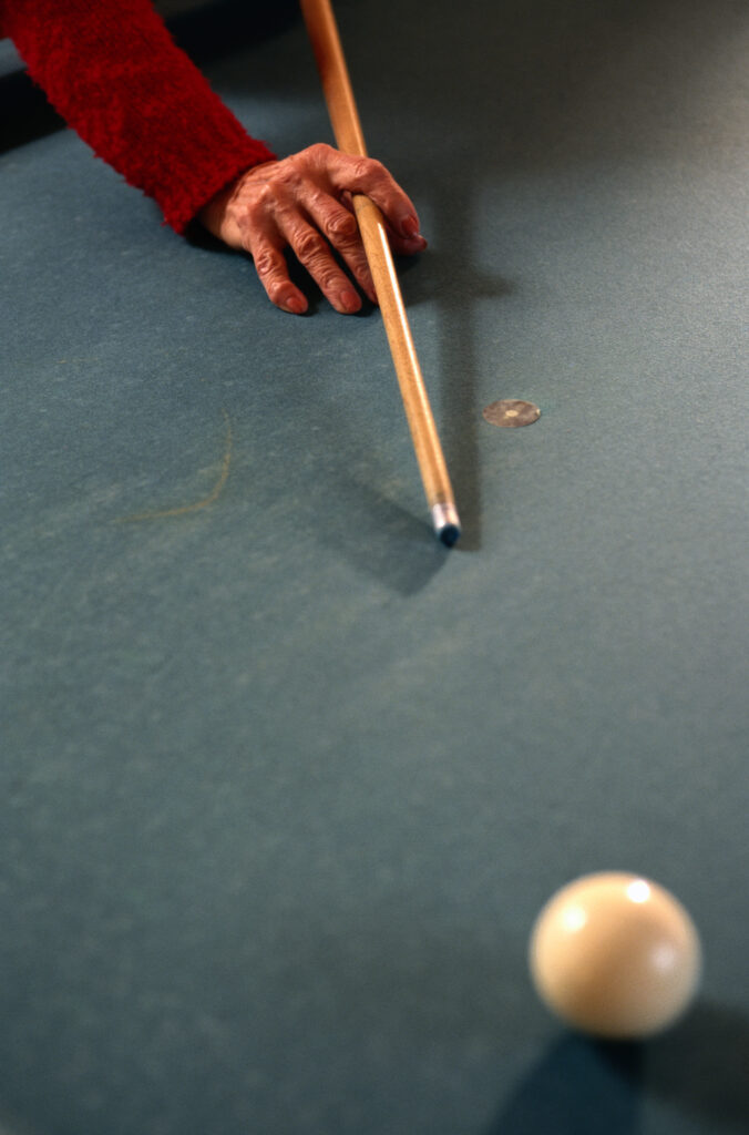 Person holding a pool cue aiming for a ball
