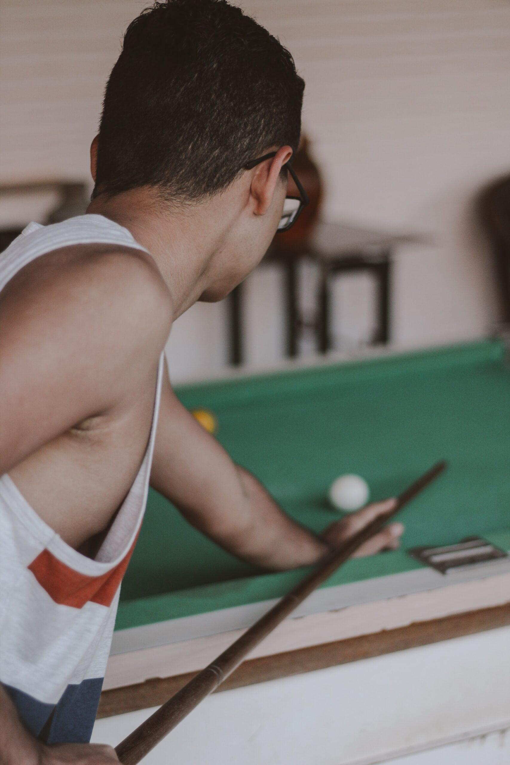 Man in white tank top playing billiards