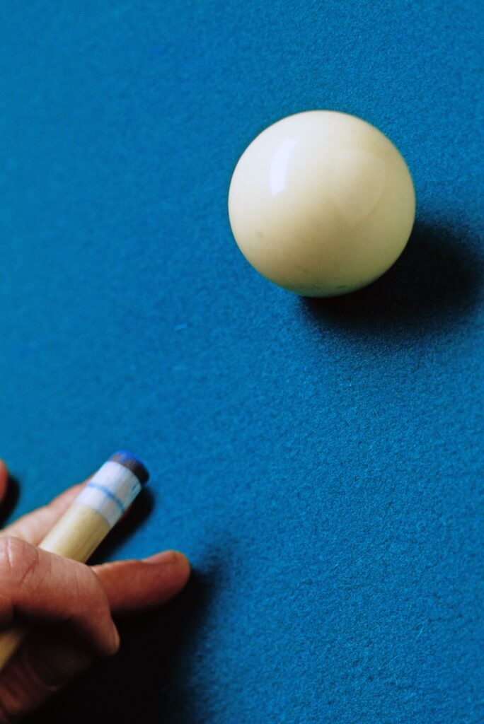 Person aiming to hit a cue ball