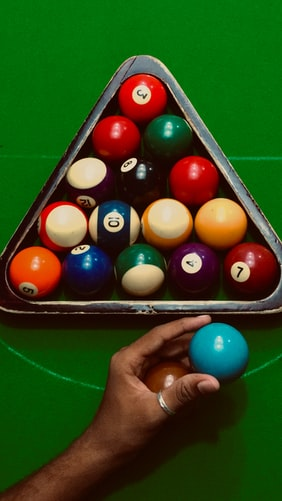 Person putting the cue balls in a pool rack