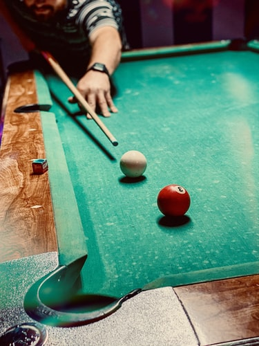Person playing a game of pool