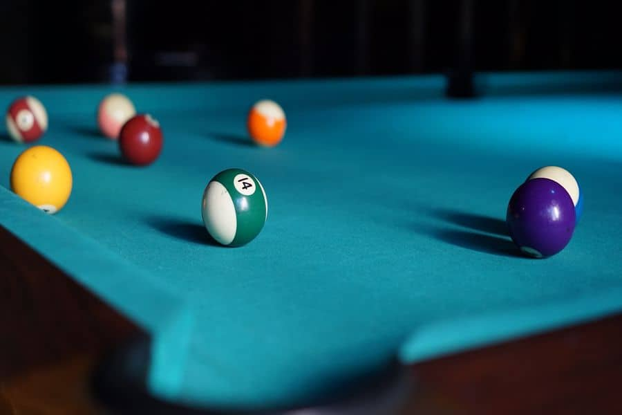 Pool table with cue balls scattered on top