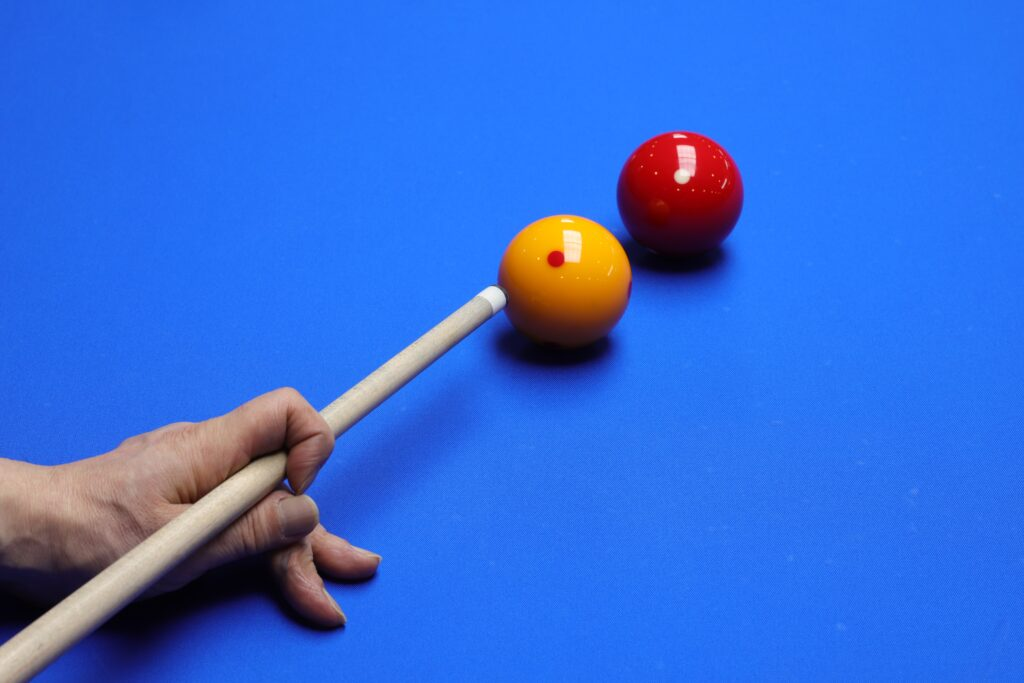 A yellow cue ball and a red ball on a blue billiards table
