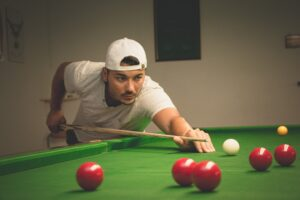 A person playing snooker with red balls