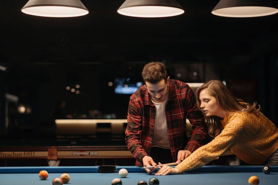 Man teaching a woman how to hold a pool cue stick
