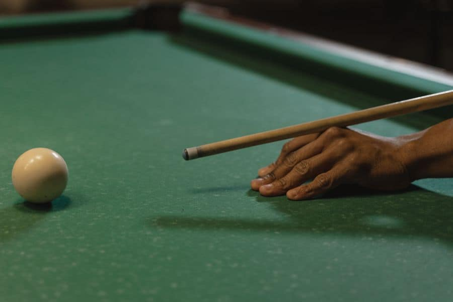 Person aiming at a cue ball