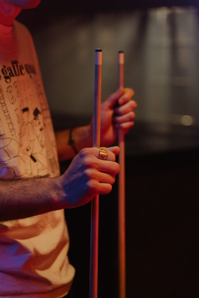 Person holding two cue sticks