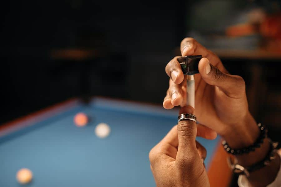 Person using chalk in a pool cue tip