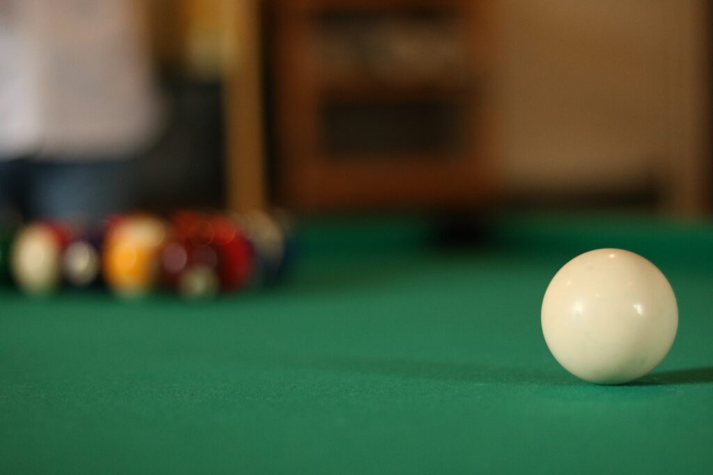 A white cue ball with a pool set up and a green table felt cloth