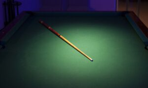 A cue stick on a green billiard table with spotlight