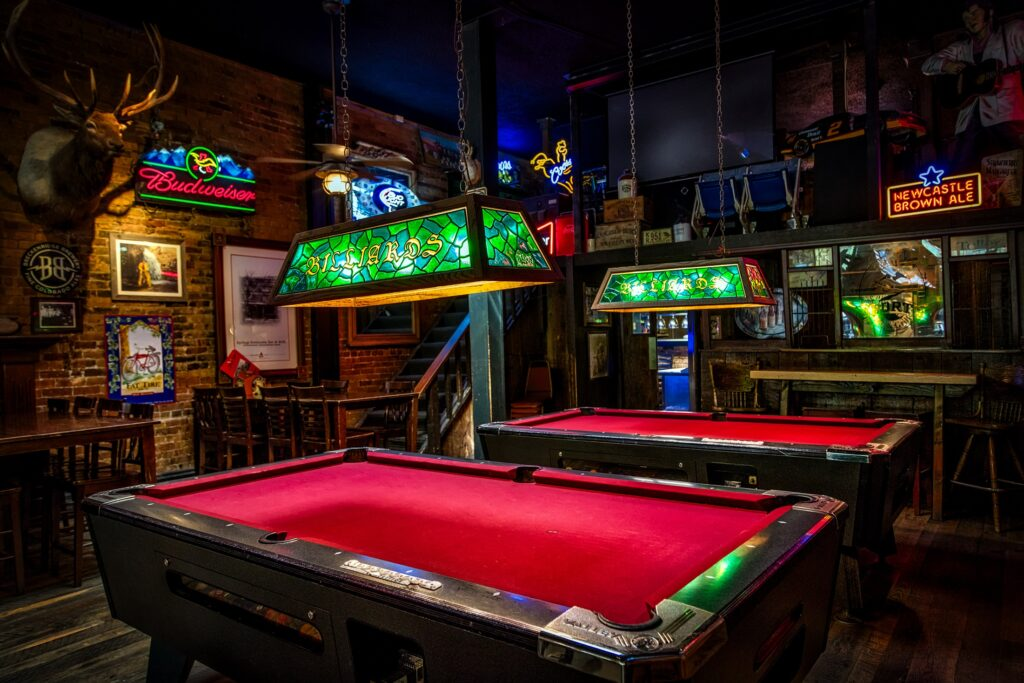Red pool tables with lights inside a bar