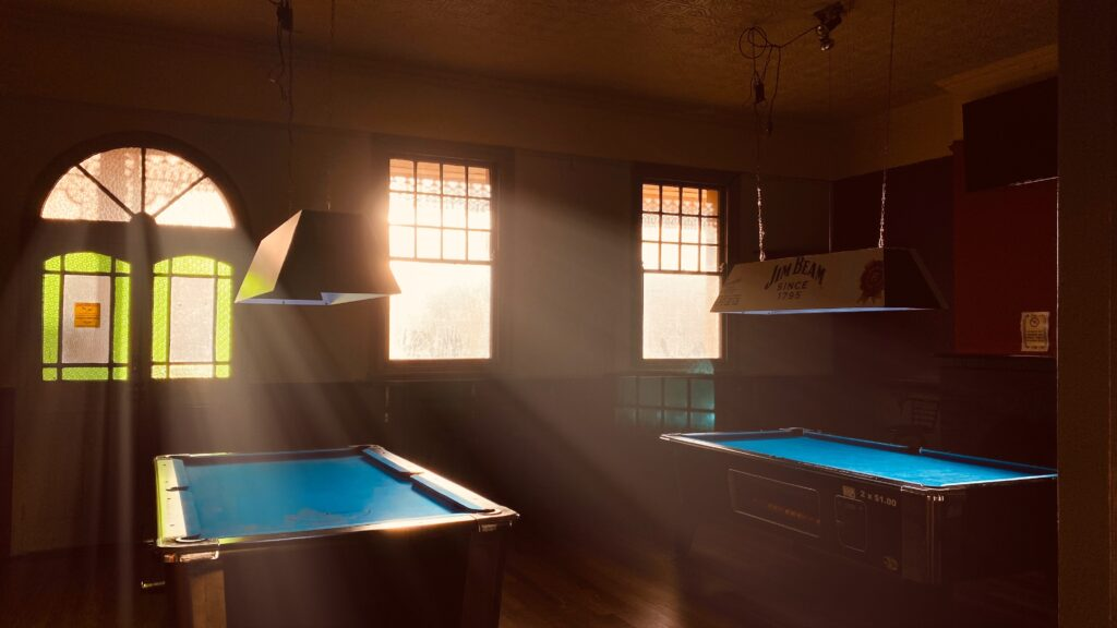 Two blue pool tables near the window and the door