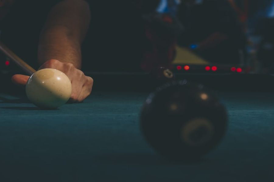 Person aiming the pool cue at a cue ball