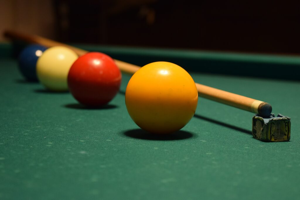 A pool stick with four pool balls on a billiard table