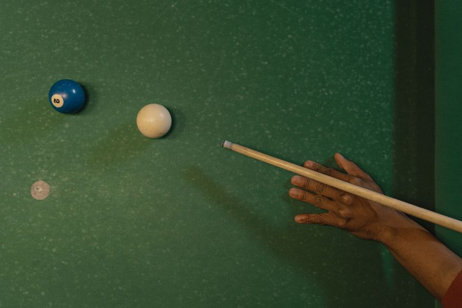 Person aiming a cue stick at a ball