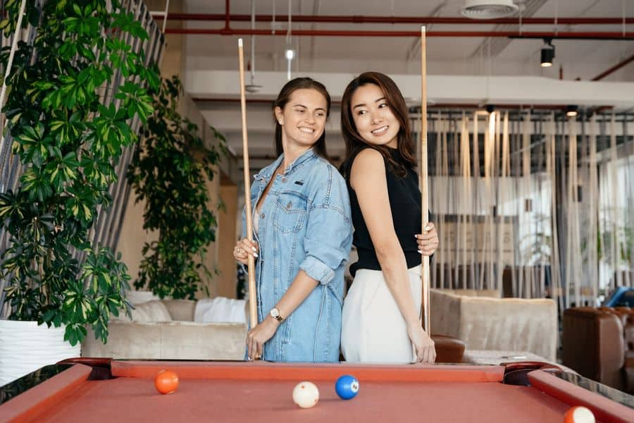 Two women standing side by side holding a pool cue