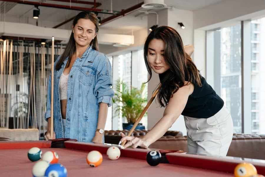 Woman looking over her friend while she's aiming to hit a pool ball
