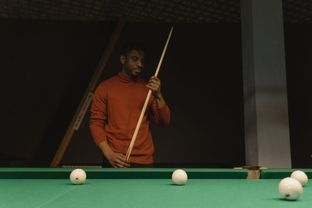 A person standing beside a pool table holding a cue