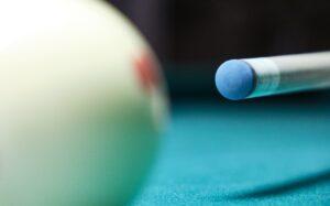 A close up shot of a tip of a cue and a white cue ball